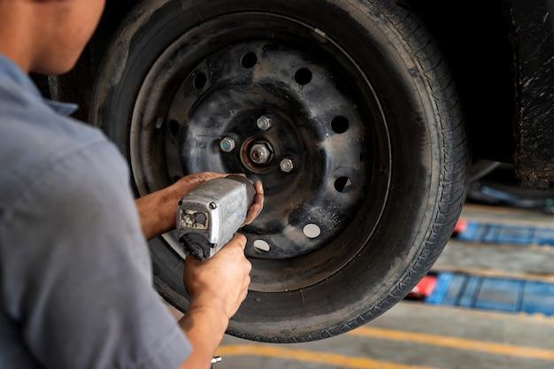 Automechanikermann mit elektrischem schraubendreher, der reifen in autowerkstatt wechselt.