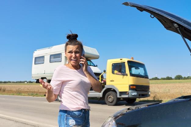 Autopanne, unglückliche frau auf der straße mit offener motorhaube, die mit dem handy spricht. autoreparaturservice, transport, abschleppwagenanruf