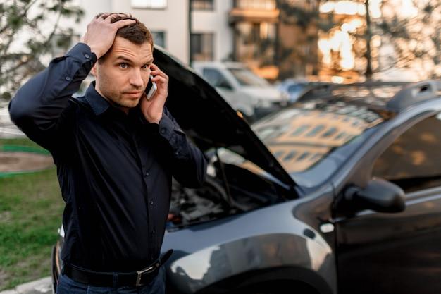 Autopannenkonzept. das auto springt nicht an. ein junger mann ruft nach einem autoservice. sie können das auto nicht selbst reparieren. die versicherung muss alle kosten decken.