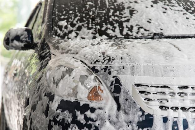 Autopflegepersonal, das das auto säubert (autodetails).