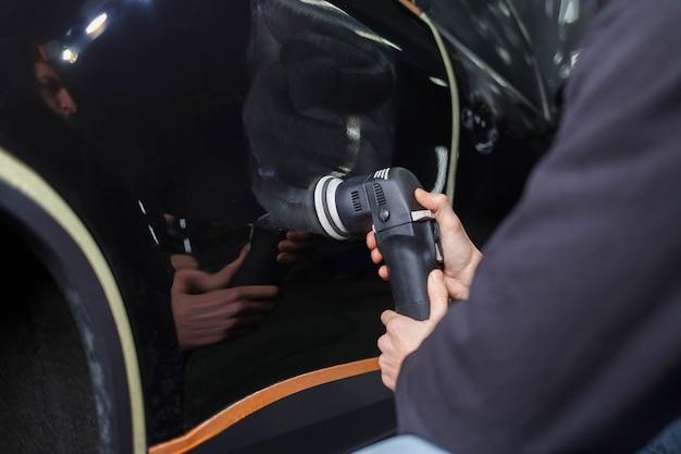 Autopolierprozess. detailarbeiter poliert karosserie