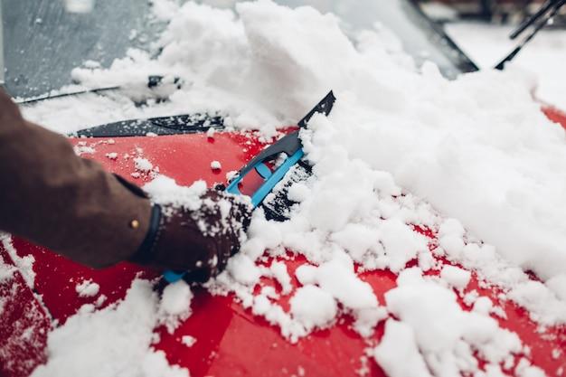 Autoreinigung vom schnee unter verwendung des besens. bemannen sie um dem automobilstoßdämpfer sich kümmern, der draußen eis mit bürste entfernt