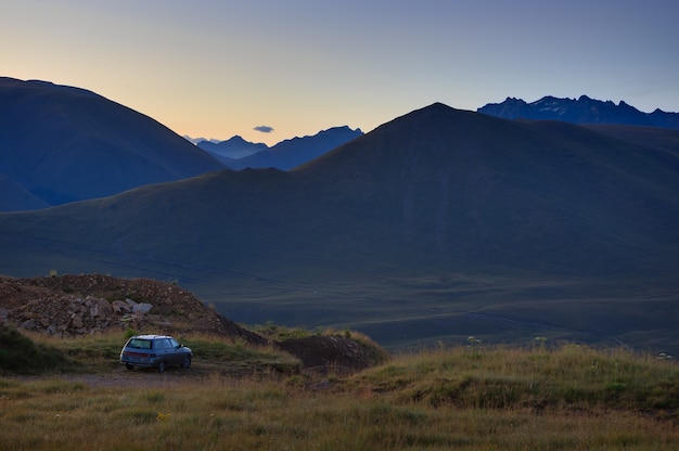 Autoreisende bei sonnenuntergang in den bergen im nordkaukasus in russland.