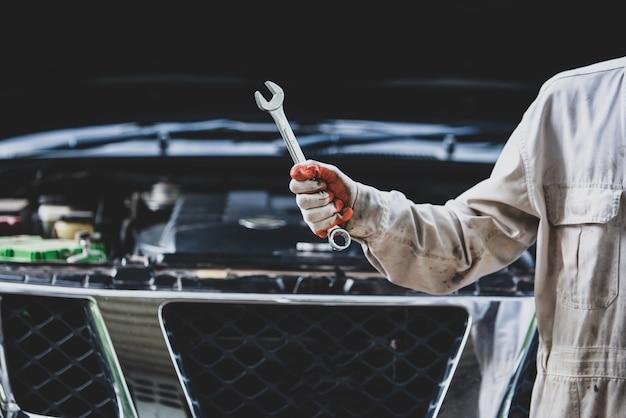 Autoreparaturmann, der eine weiße uniform steht und einen schlüssel hält, der ein wesentliches werkzeug für einen mechaniker ist