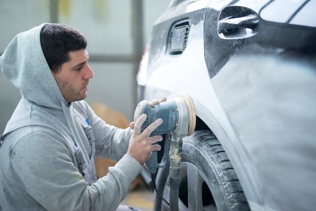 Autoreparaturmann, der karosserie mit einer maschine schleift, die fahrzeug zum lackieren vorbereitet