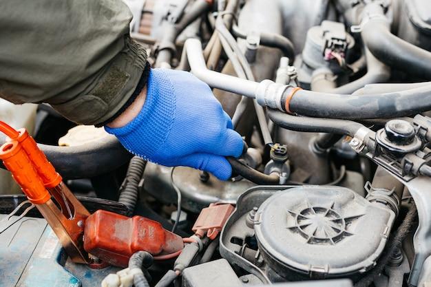 Autoreparaturservice. automechaniker, der das auto repariert und die wartung umfassend überprüft. der automechaniker in blauen handschuhen hat eine panne festgestellt und weist auf eine fehlfunktion hin.