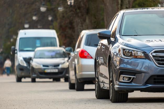 Autos, die an einem hellen herbsttag in einer reihe auf einer straßenseite der stadt geparkt sind.