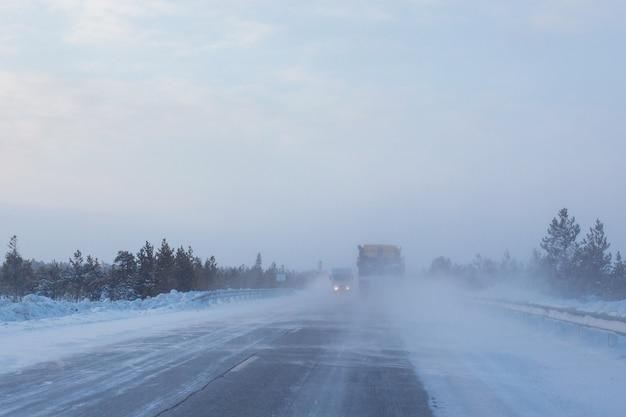 Autos fahren auf einer winterstraße mit schlechter sicht, wetter und schneesturm