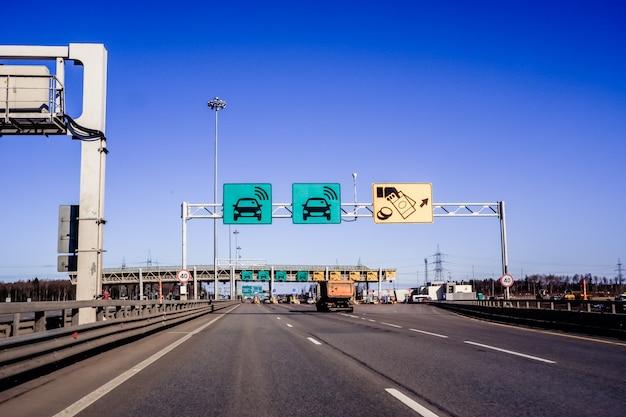 Autos fahren durch den punkt der gebührenpflichtigen autobahn, mautstation. der westliche hochgeschwindigkeitsdurchmesser ist eine schnellstraße durch die stadt, sankt petersburg, russland. autobahn mautstelle. russische straßen