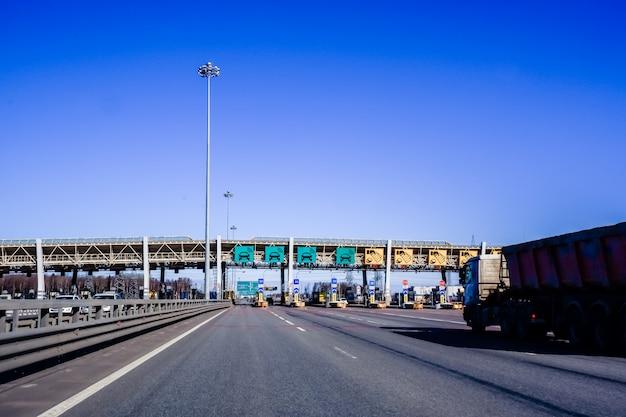 Autos fahren durch den punkt der gebührenpflichtigen autobahn, mautstation. der westliche hochgeschwindigkeitsdurchmesser ist eine schnellstraße durch die stadt, sankt petersburg, russland. autobahn mautstelle.