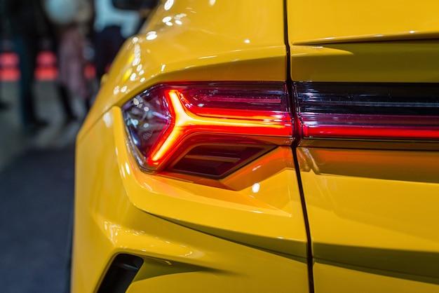 Autoscheinwerfer mit hintergrundbeleuchtung. außendetail. gelbfarbiges luxusauto