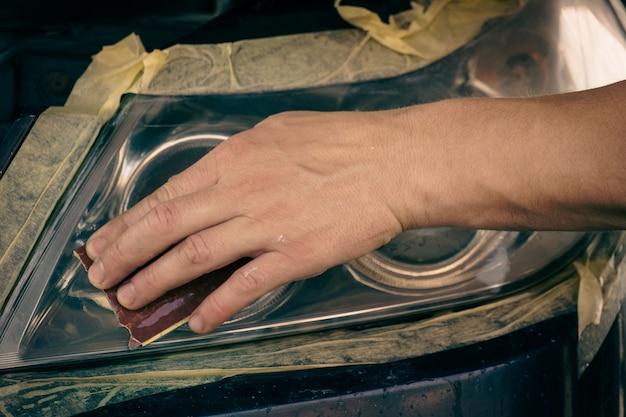 Autoscheinwerfer reinigen. der meister reinigt die scheinwerfer mit feinem schleifpapier.