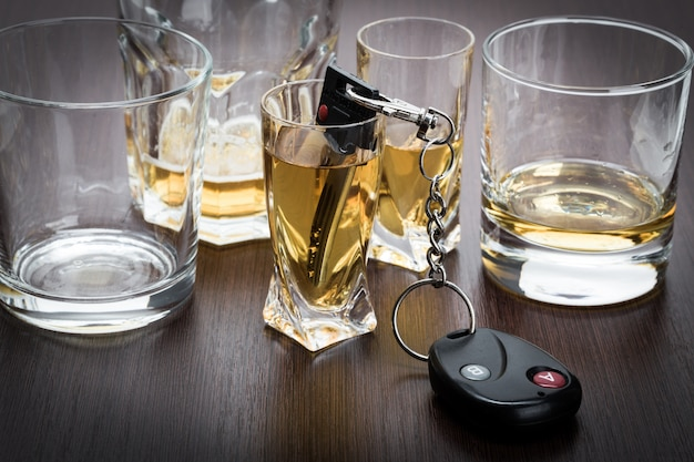 Autoschlüssel auf der bar mit verschüttetem alkohol