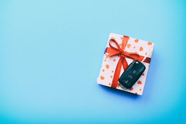 Autoschlüssel auf papiergeschenkbox mit rotem bandbogen und herz auf blauem tabellenhintergrund. feiertagsgeschenk-draufsichtkonzept