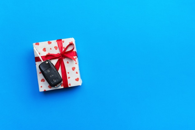 Autoschlüssel auf papiergeschenkbox mit rotem bandbogen und herz auf blauer tabelle. copyspace. feiertagsgeschenk-draufsichtkonzept