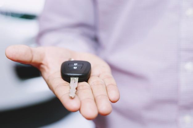 Autoschlüssel, geschäftsmann übergibt den autoschlüssel an den anderen mann auf dem autotisch.