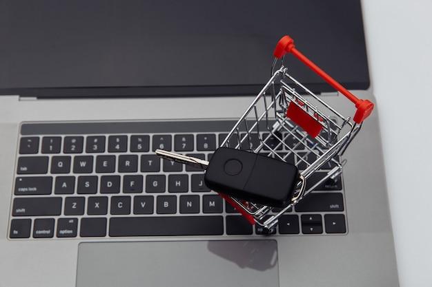 Autoschlüssel im einkaufswagen auf einer laptoptastatur.