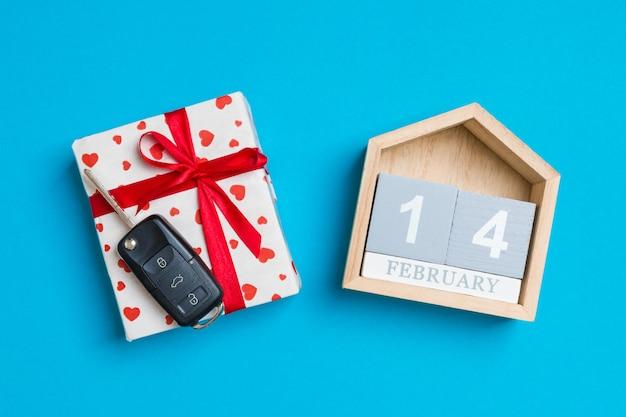 Autoschlüssel in einer geschenkbox mit roten herzen und festlichem kalender