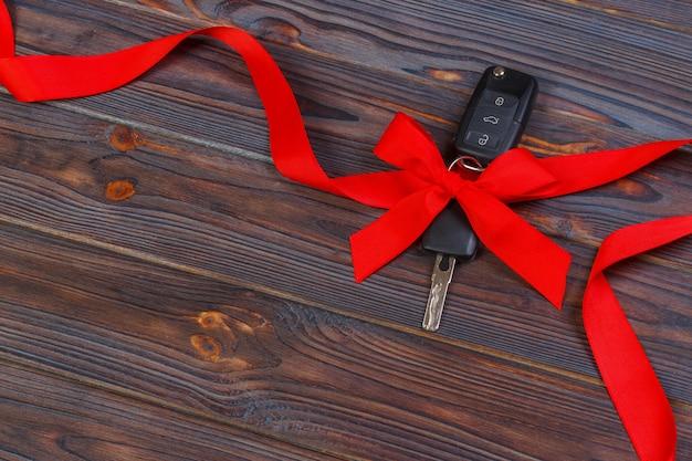 Autoschlüssel mit buntem bogen auf holz