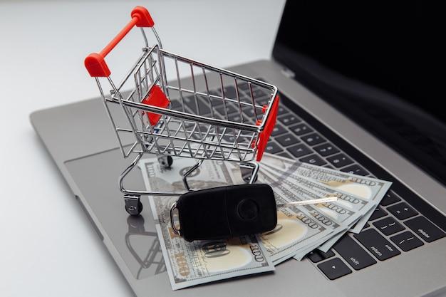 Autoschlüssel mit dollarbanknoten und einkaufswagen auf tastatur. online-kauf auto konzept.