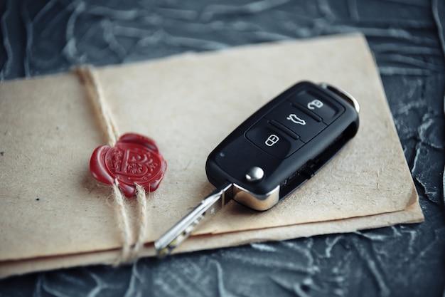 Autoschlüssel und umschlag auf dem schreibtisch