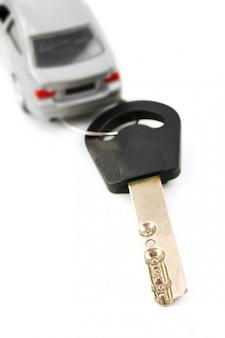 Autoschlüssel und unbekanntes auto in unschärfe