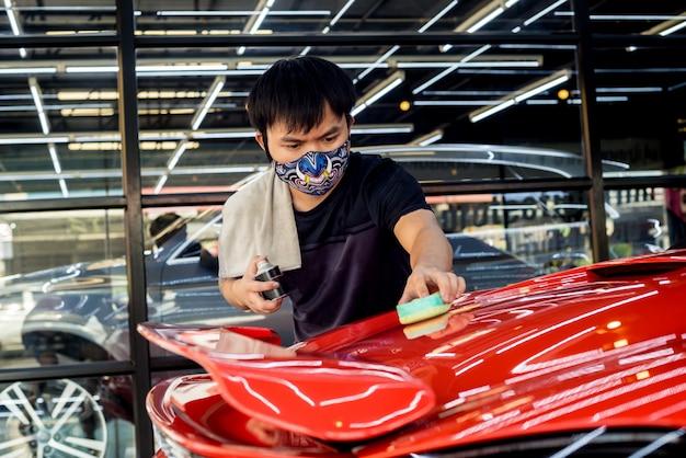 Autoservice-arbeiter, der eine nanobeschichtung auf ein autodetail aufträgt
