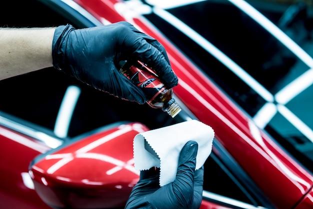 Autoservice-arbeiter, der nanobeschichtung auf einem auto anbringt
