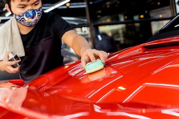 Autoservice-arbeiter, der nanobeschichtung auf einem auto aufbringt