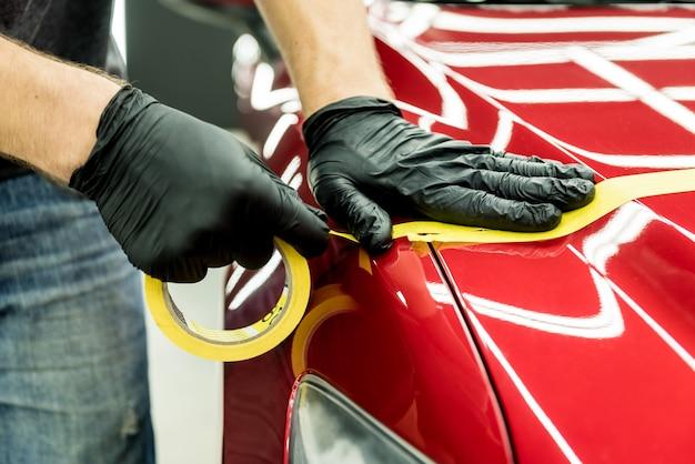Autoservice-arbeiter, der schutzband auf dem auto anbringt