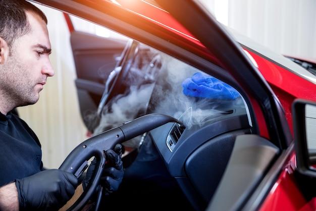 Autoservice-mitarbeiter reinigt den innenraum mit dampfreiniger