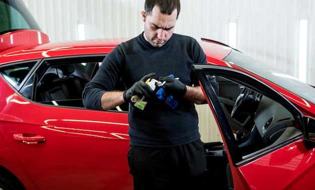 Autoservice-mitarbeiter reinigt den innenraum mit spezialbürste