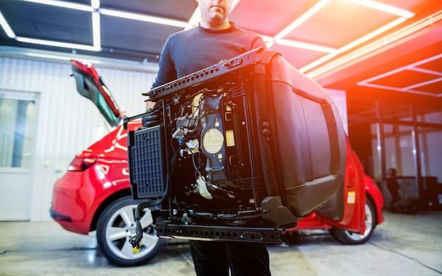 Autoservice-mitarbeiter zerlegen den innenraum des autos
