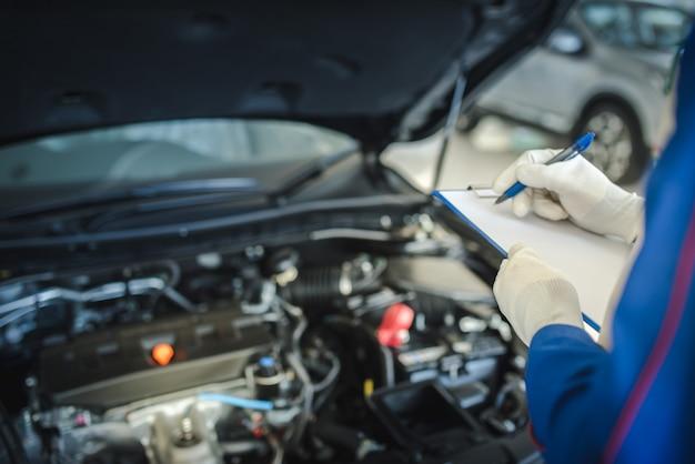 Autoservice-, reparatur-, wartungskonzept - asiatischer automechaniker oder smith, der in der werkstatt oder im lager in die zwischenablage schreibt, techniker, der die checkliste für die reparaturmaschine für ein neues auto erstellt