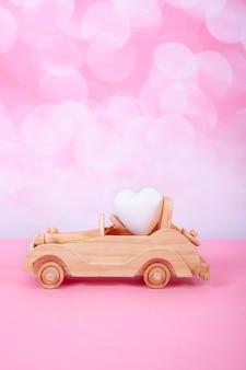 Autospielzeug mit einem geschenk und einem bogen in form eines herzens auf einem rosa hintergrund mit bokeh