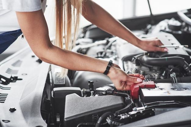 Autosüchtige frau repariert tagsüber schwarzes auto drinnen in der garage