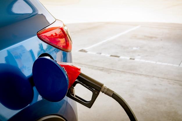 Autotank an der tankstelle. tanken sie benzin nach. kraftstoffpumpe der benzinpumpe im kraftstofftank des autos an der tankstelle. benzinindustrie und service ..