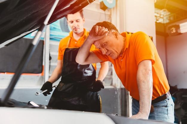 Autotechniker-ingenieur-service-team betonte kranker, müder mann, der probleme mit dem motor des kunden hatte, der die motorhaube in der autogarage betrachtete