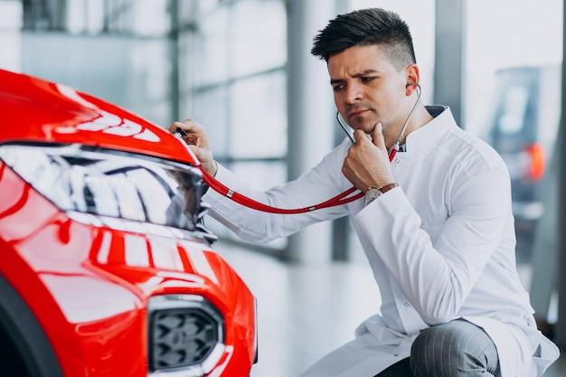 Autotechniker mit stethoskop in einem autosalon