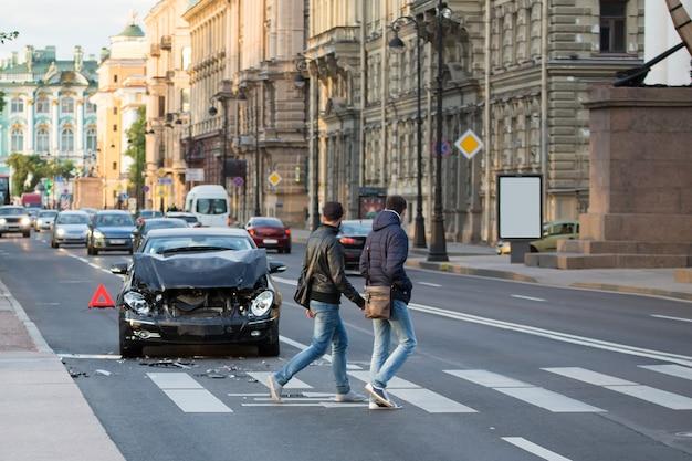 Autounfall unfallstelle auf der stadtstraße. abgestürztes fahrzeug auf der straße wartet auf polizei und notfall