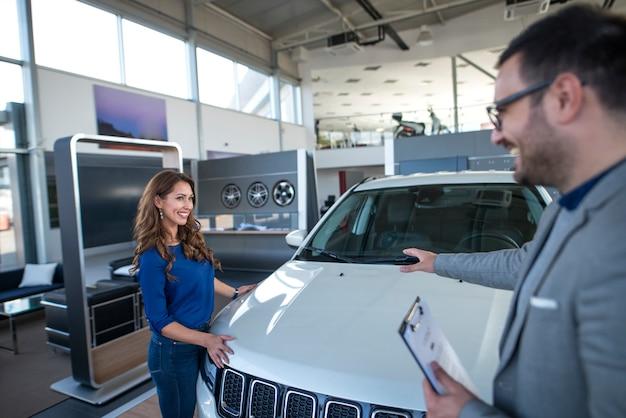 Autoverkäufer, der dem kunden fahrzeug präsentiert