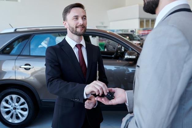 Autoverkäufer, der dem kunden schlüssel gibt