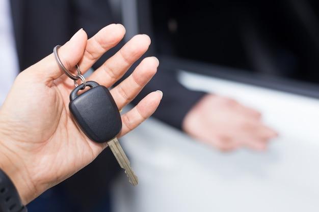 Autoverkäufer, der den schlüssel übergibt