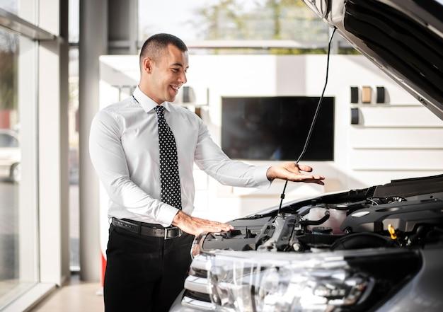 Autoverkäufer, der ein auto überprüft