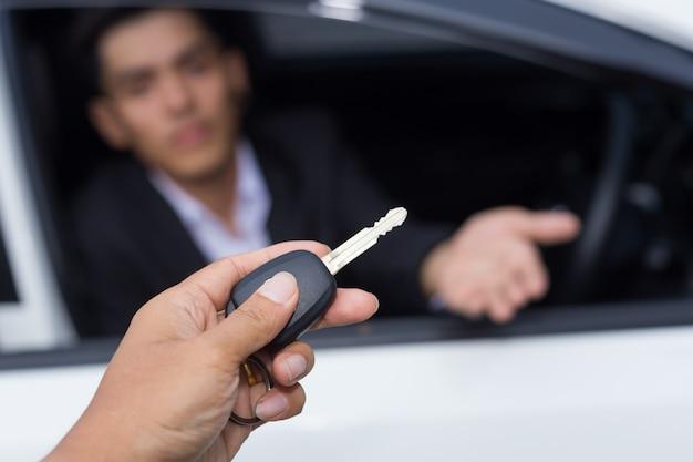 Autoverkäufer, der einem jungen geschäftsmann vor dem weißen auto den schlüssel für einen neuwagen überreicht