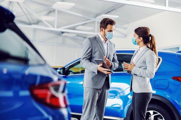 Autoverkäufer, der im autosalon mit einem kunden steht, der gesichtsmasken trägt und details auf einem tablett zeigt.
