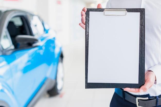 Autoverkäufer, der klemmbrettschablone zeigt