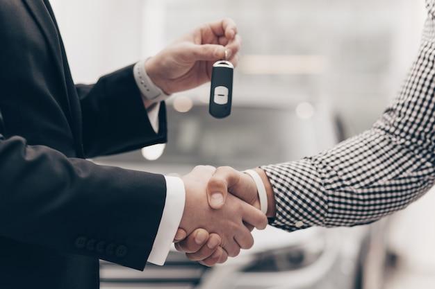 Autoverkäufer, der mit einem kunden an der verkaufsstelle arbeitet