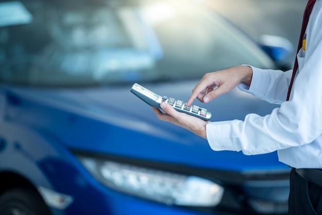 Autoverkäufer, der taschenrechner für geschäftsfinanzierung auf autosalon drückt neues blaues auto