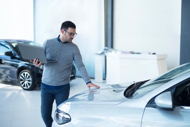Autoverkäufer mit laptop, der die fahrzeugspezifikationen im ausstellungsraum des örtlichen händlers überprüft